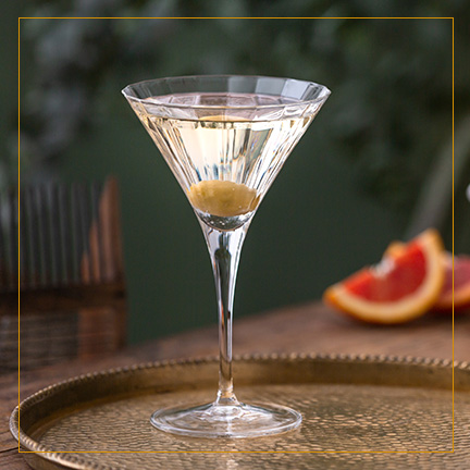 Dry Martini Cocktail with olive on brass plate