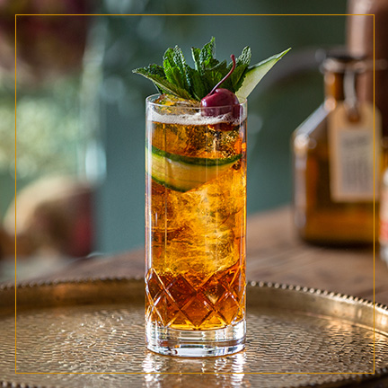 Pimms Cup Cocktail in Highball Glass on brass plate