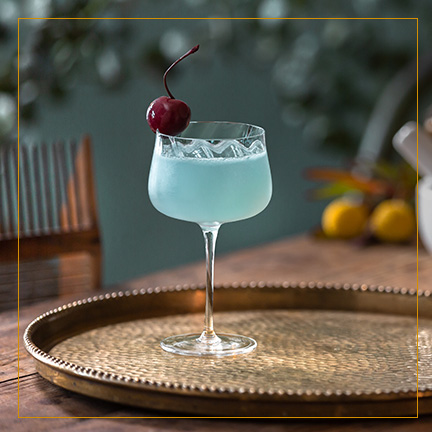 Aviation Cocktail on brass plate with cherry